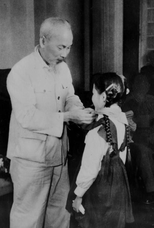 Chủ tịch Hồ Chí Minh quàng khăn đỏ cho đại biểu thiếu nhi Thủ đô đến chúc mừng kỷ niệm 30 năm Ngày thành lập Đảng (1960). (Ảnh: Tư liệu TTXVN)